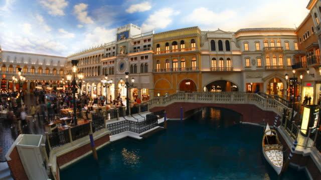tourists walk around and take gondola rides at the venetian hotel in las vegas. - the strip las vegas stock videos & royalty-free footage