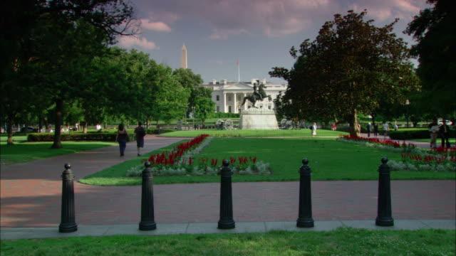 Tourists walk around Lafayette Park near the Andrew Jackson statue.