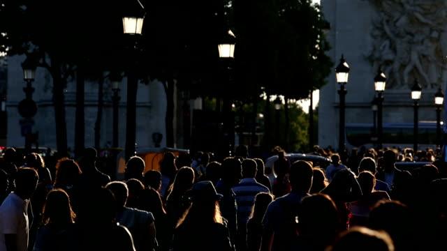 Touristes descendent les Champs-Elysées avec soleil fin de l'après-midi