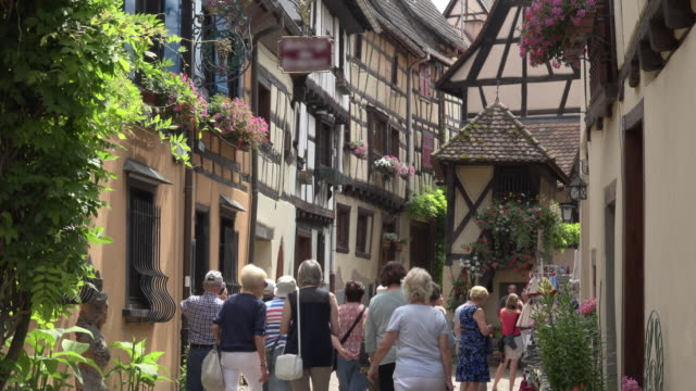 tourists walk in a alley with half-timbered house in a picturesque village - dorf stock-videos und b-roll-filmmaterial