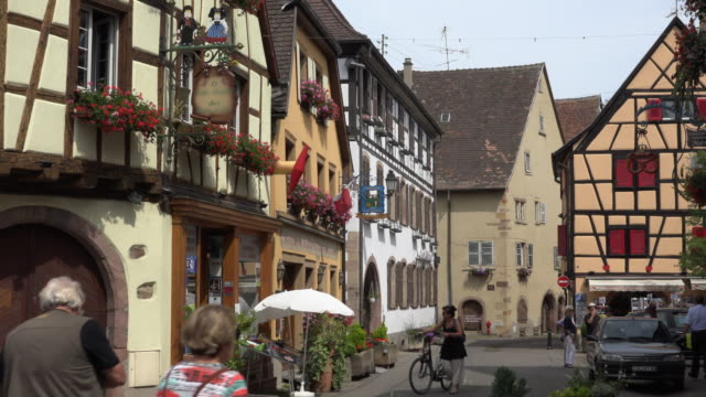tourists walk in a picturesque village with half-timbered houses - france stock videos & royalty-free footage