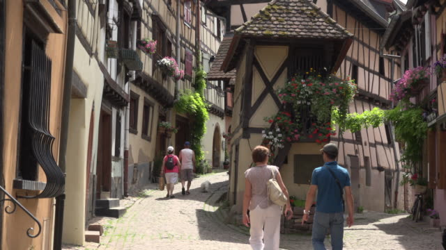 Tourists walk in alley with half-timbered house in a picturesque village