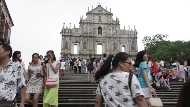 tourists walk in front of the ruins of st. paul's cathedral in macau, china, on sunday, aug. 28 the casino grand lisboa, operated by sjm holdings... - 聖ポール天主堂跡点の映像素材/bロール