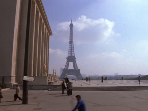 tourists walk in the foreground of the eiffel tower. - eiffel tower paris stock videos & royalty-free footage