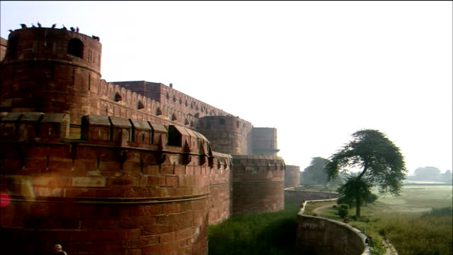 Tourists walk over a bridge to the main gate of the Agra Fort in India.