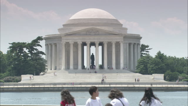 Tourists walk past the Thomas Jefferson Memorial on the other side of the Potomac River.
