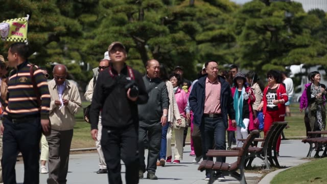 tourists walk past tour buses parked outside the imperial palace in tokyo japan on friday april 15 a tour bus drives past parked tour buses tourists... - 観光点の映像素材/bロール