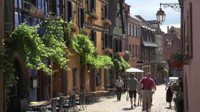 vidéos et rushes de tourists walk through a picturesque village - village