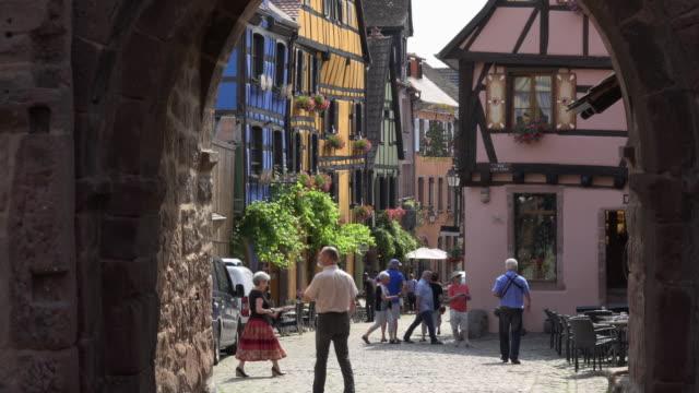 vidéos et rushes de zo / tourists walk through a picturesque village - village