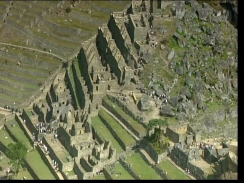 tourists walk through machu picchu peru - machu picchu stock videos and b-roll footage