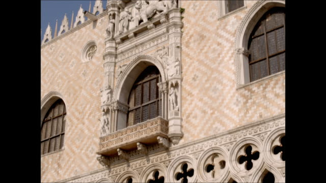 Tourists walk through Saint Mark's Square in front of Doge's Palace in Venice, Italy.