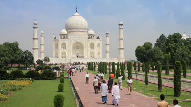 tourists walk through the gardens surrounding the taj mahal in agra, india. - agra stock videos and b-roll footage