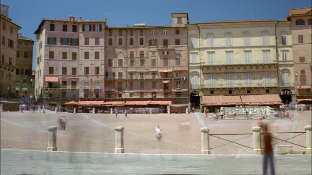 tourists walk through the piazza del campo. - piazza del campo stock videos and b-roll footage