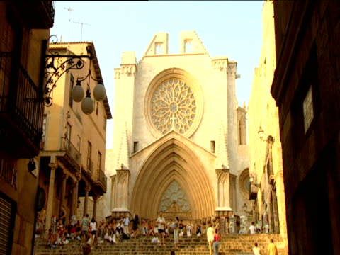 Tourists walk up steps towards Tarragona Cathedral with ornate rose window and arch over entrance