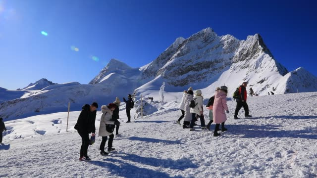 tourists walk with jungfrau summit in the background at jungfraujoch highest railway station in europe in the bernese alps mountain range on december... - european alps stock videos & royalty-free footage