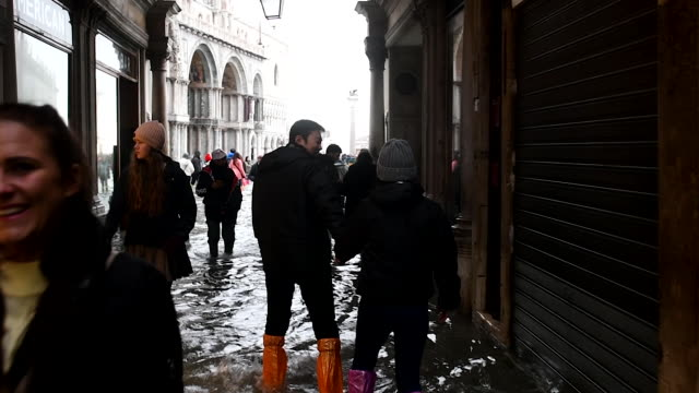 tourists walked through flooded roads during an exceptional high tide on november 13, 2019 in venice, italy. venice second highest tide after 1966... - venedig stock-videos und b-roll-filmmaterial