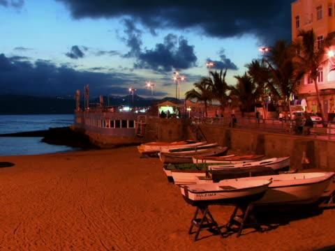 t/l ws tourists walking along promenade near empty rowboats on beach at dusk / las palmas de gran canaria, spain - unknown gender stock videos & royalty-free footage