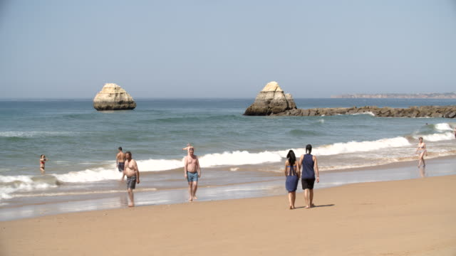 Tourists walking along the beach / Algarve, Portugal