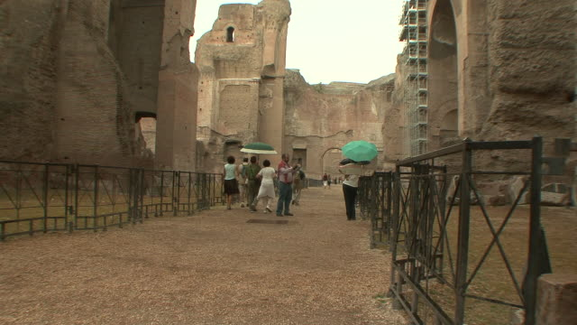 ws tu td tourists walking and photographing under rain in main isle of baths of caracalla / rome, italy   - baths of caracalla stock videos and b-roll footage