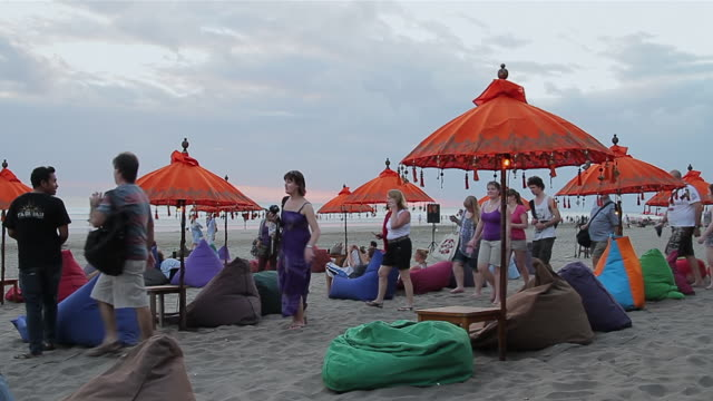 ms tourists walking and relaxing on beach at dusk / seminyak, bali, indonesia - indonesia beach stock videos & royalty-free footage