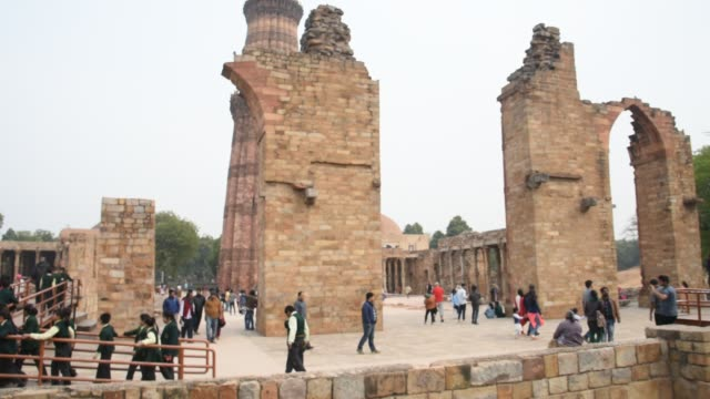 tourists walking and watching qutub minar, delhi, india. - mosque stock videos & royalty-free footage