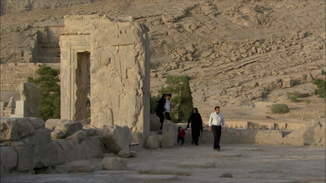 ws tourists walking around ancient city, throne room, persepolis, iran - persepoli video stock e b–roll