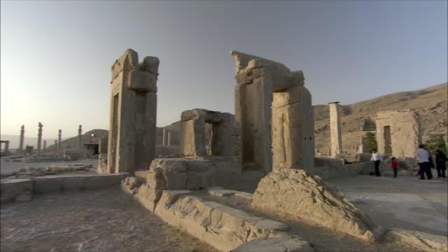 ws pan tourists walking around ancient city, throne room, persepolis, iran - persepoli video stock e b–roll