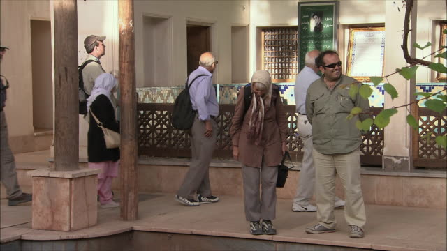 ws tourists walking around courtyard inside village mosque, abyaneh, iran - besichtigung stock-videos und b-roll-filmmaterial