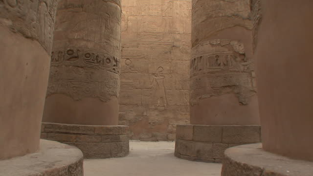 ws tourists walking by giant pillars in hypostyle hall in karnak, luxor, egypt - temples of karnak stock videos & royalty-free footage
