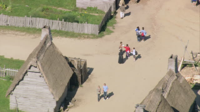 aerial tourists walking by historical cottages and artifacts at plimoth plantation / plymouth, massachusetts, united states - pellegrino video stock e b–roll