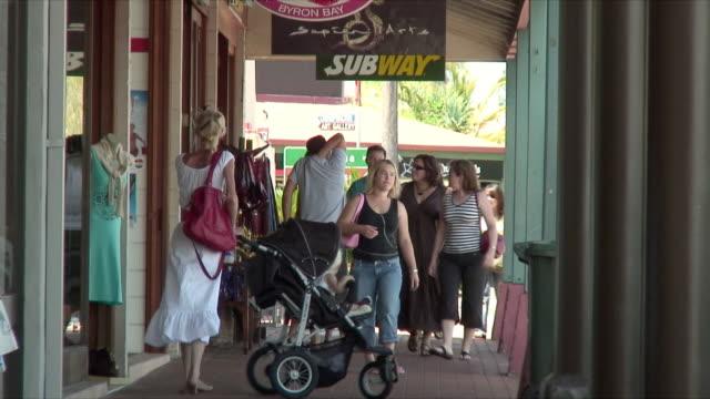 zo ms tourists walking down street window shopping, byron bay, queensland, australia - three wheeled pushchair stock videos & royalty-free footage