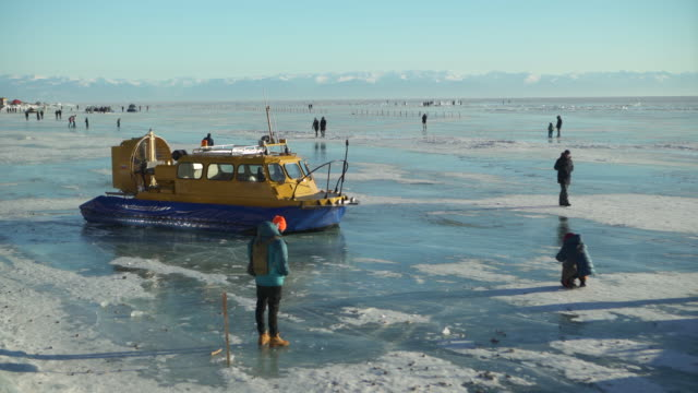 tourists walking frozen lake baikal against sky - hovercraft stock videos & royalty-free footage