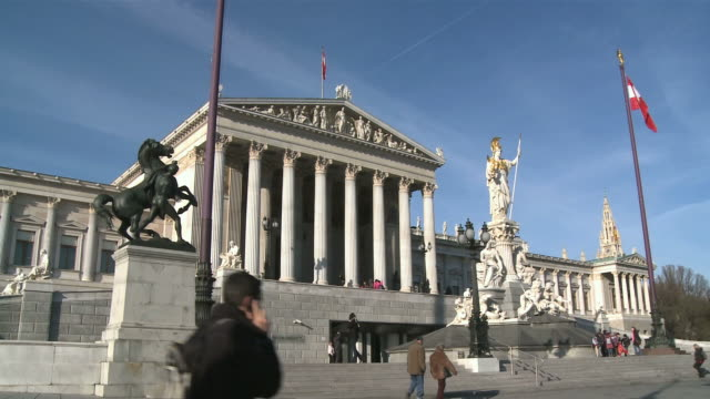 ws tourists walking in front of austrian parliament and pallas athene statue at dr. karl lueger ring / vienna, austria - オーストリア文化点の映像素材/bロール