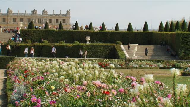 stockvideo's en b-roll-footage met ws tourists walking in garden, palace in background / versailles, ile de france, france - versailles