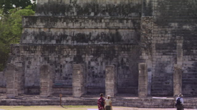 ws pan tourists walking near temple and looking at stone statue at ancient mayan site chichen itza / yucatan, mexico  - ca. 7 jahrhundert stock-videos und b-roll-filmmaterial