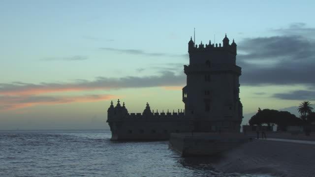 WS Tourists walking near Torre de Belem at dusk / Lisbon, Portugal