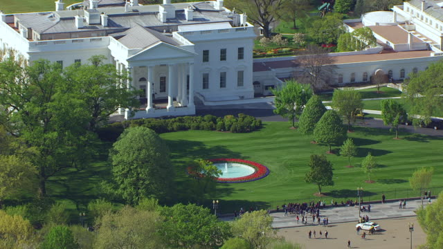 ms zo aerial pov tourists walking near white house in front of gate, lawn in foreground / washington dc, united states - la casa bianca washington dc video stock e b–roll