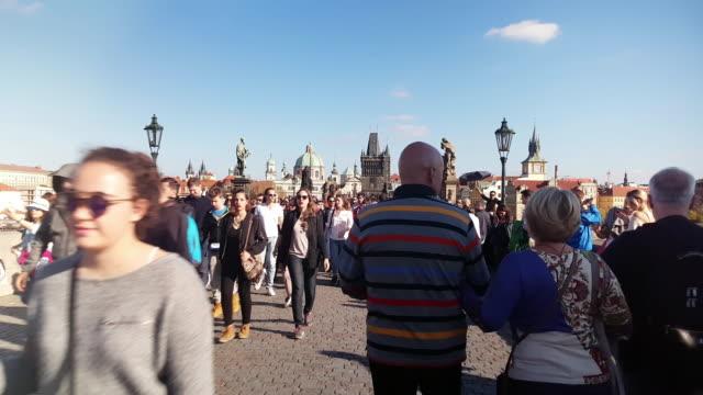 tourists walking on prague charles bridge - charles bridge stock videos & royalty-free footage