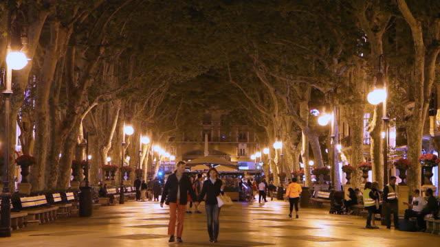 tourists walking on the central illuminated street of palma de mallorca, balearic islands, spain - palma stock videos & royalty-free footage