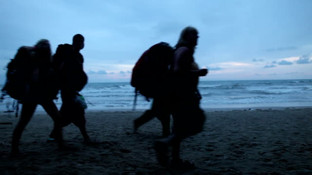 Tourists walking on the evening tropical beach.