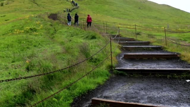 Tourists walking on the staircase at skogafoss waterfall in Iceland, slow motion