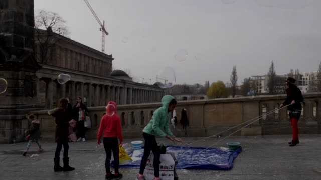 tourists walking over friedrichsbrücke bridge as children play with street performers bubble display berlin germany - スプリー川点の映像素材/bロール