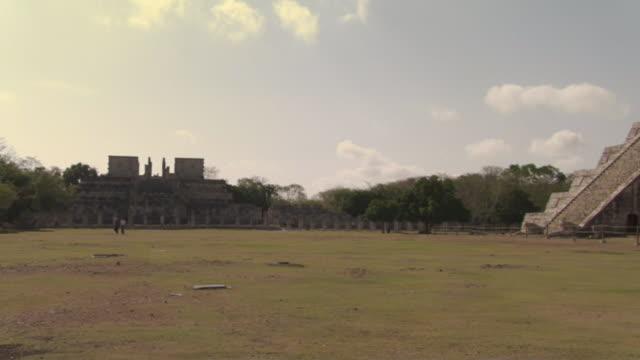 vídeos de stock e filmes b-roll de ws zi tourists walking past kukulkan pyramid near chac mool statue atop wall at ancient mayan site chichen itza / yucatan, mexico  - por volta do século 7 dc