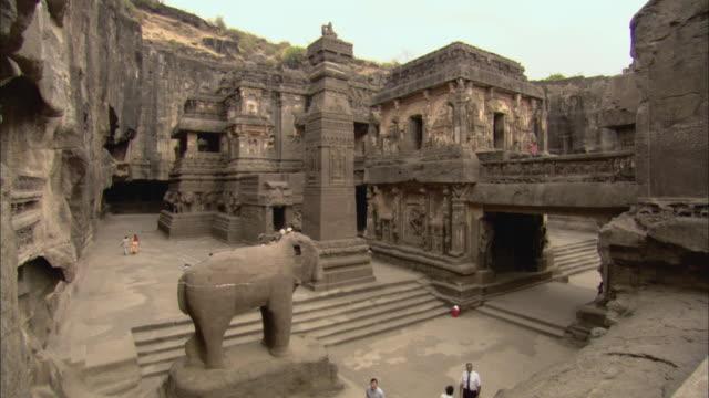 ha ws tourists walking through kailash temple, also known as kailasanatha temple / ellora, india - 寺院点の映像素材/bロール