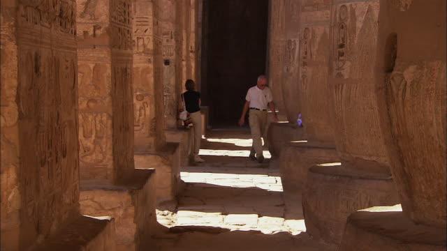 T/L WS Tourists walking through Medinet Habu (Mortuary Temple of Ramesses III) columns and hieroglyphics / Medinet Habu, Luxor Governorate, Egypt