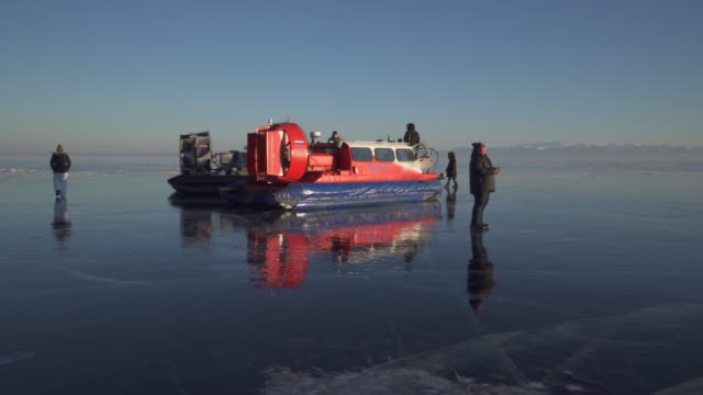 tourists walking towards hovercraft on frozen lake baikal against clear blue sky - hovercraft stock videos & royalty-free footage