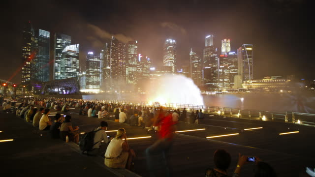Tourists watch a light and water show in Marina Bay.