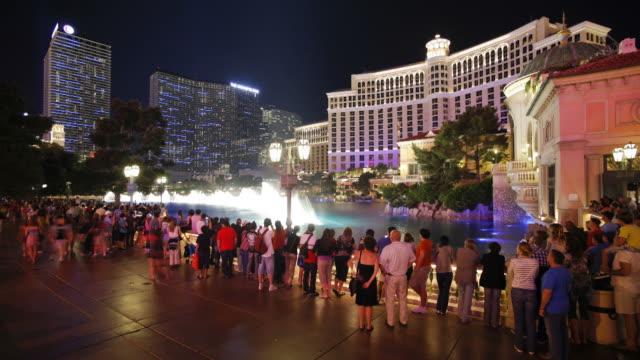 tourists watch a light show in a fountain along las vegas boulevard in las vegas. - the strip las vegas stock videos & royalty-free footage