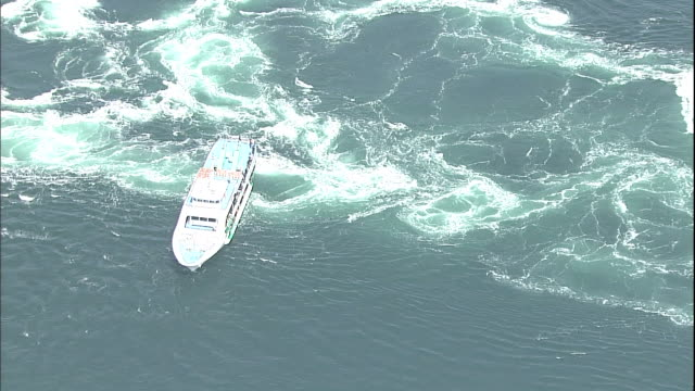 Tourists watch a whirlpool from the deck of a cruise ship in the Naruto Strait in Japan.