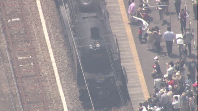 tourists watch and take pictures of the revived steam locomotive c6120 stopping at shibukawa station in gunma, japan. - locomotive点の映像素材/bロール